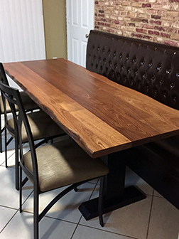 Mahogany dining table with natural edge and customized base to fit booth seating