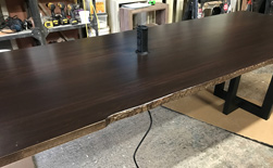 Richardson Table - Large bronze walnut table with live edge cut and grommet for a conference room